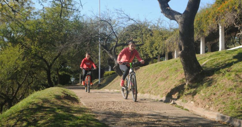 Con la mirada atenta, dos ciclistas se preparan para cruzar un tramo deteriorado de la traza de la bicisenda.