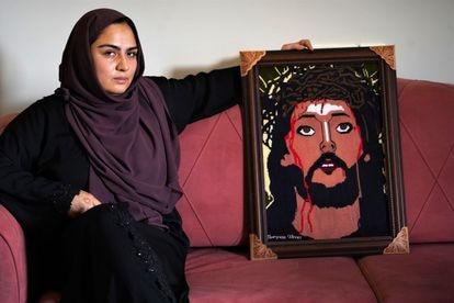 Maryam Sadat junto a un cuadro con el rostro de Cristo hecho en punto de cruz.